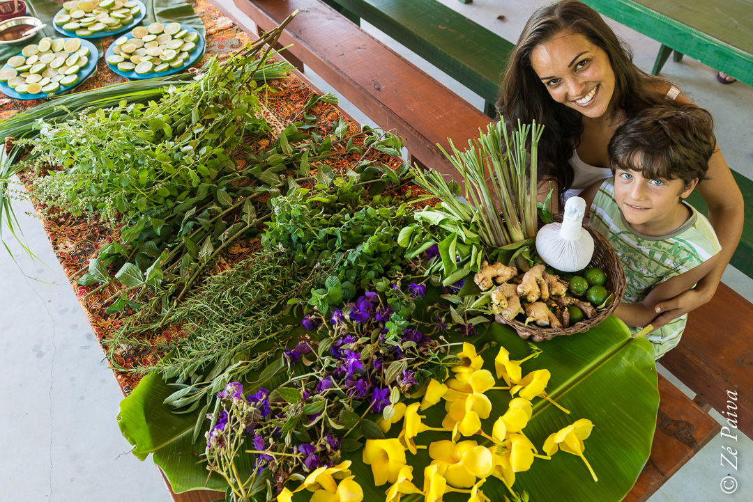 Mulher segurando criança a frente de flores e plantas sobre uma mesa