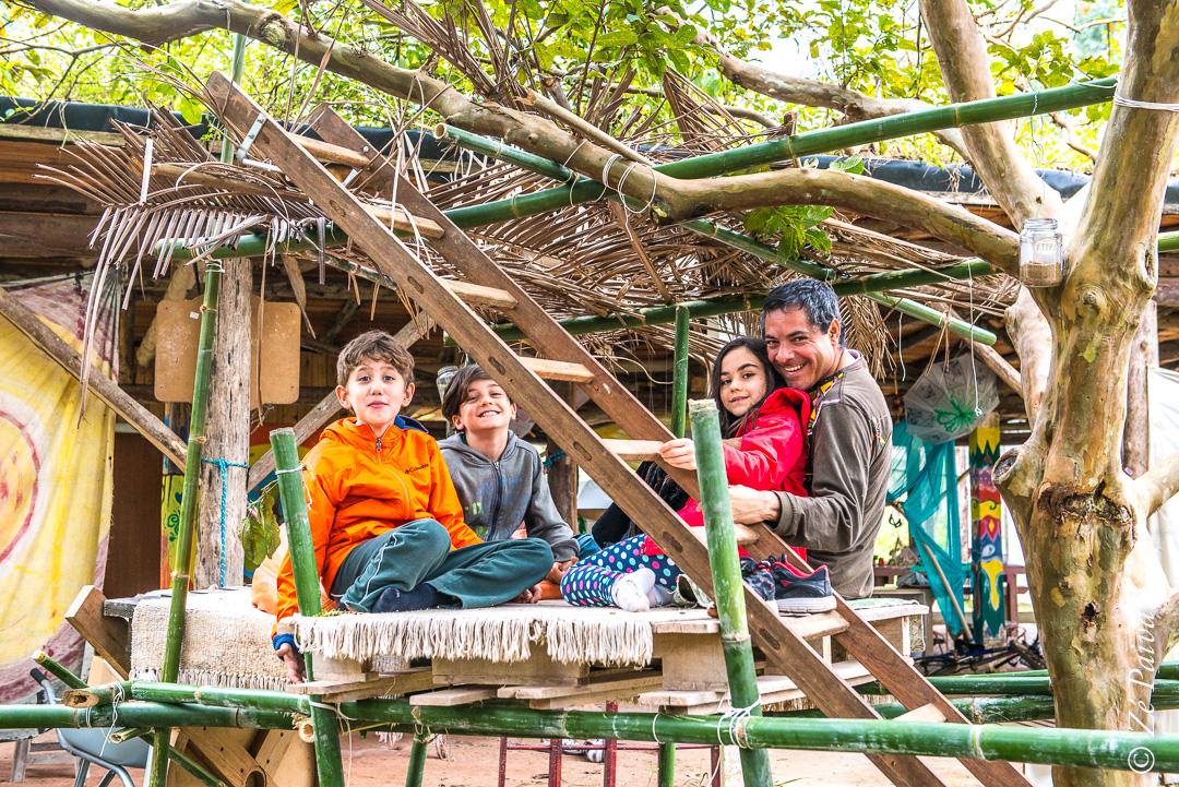 clianças acompanhadas de adulto em casinha de bambús