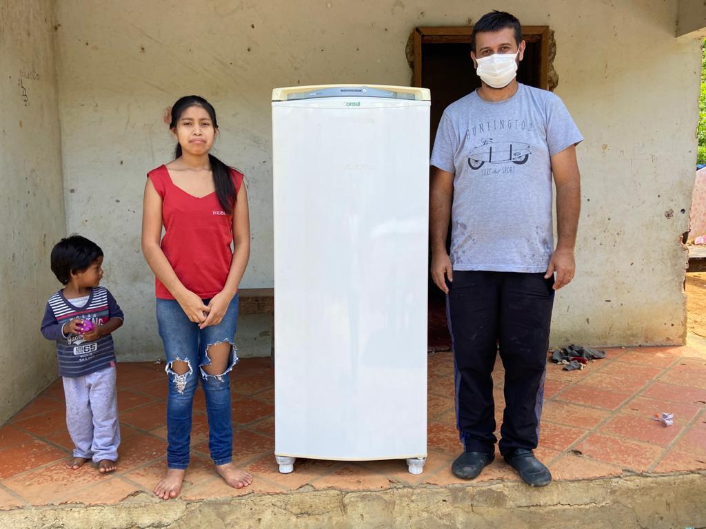 criança mulher e homem ao lado de geladeira